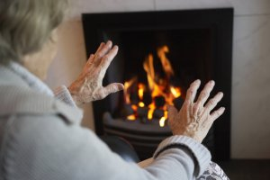elderly person warming hands in front of fire