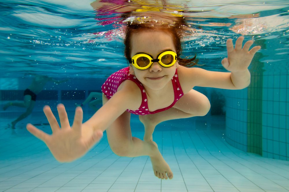 smiling girl swimming underwater
