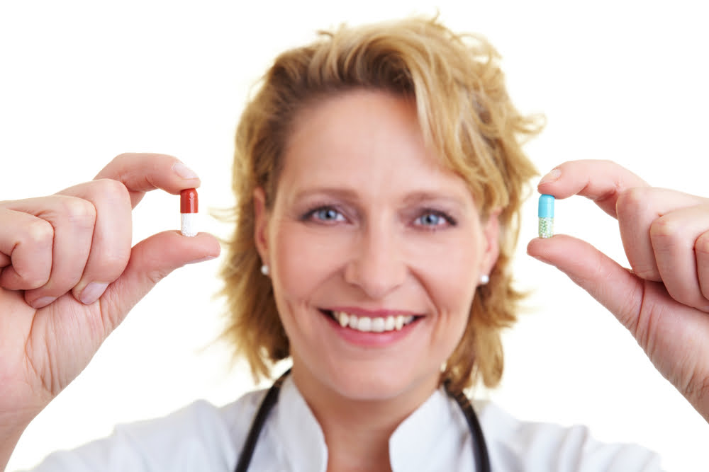 doctor holding a pill in each hand