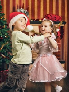 children dancing by Christmas tree