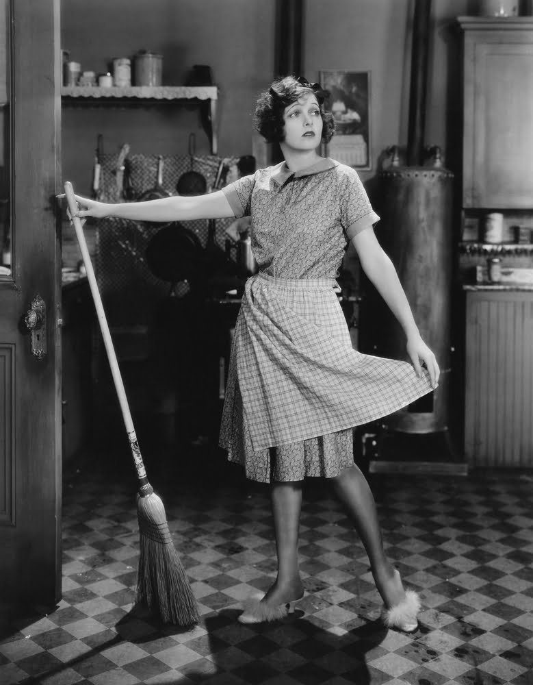 Woman standing with broom