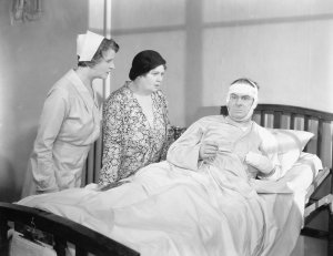 vintage photo of bandaged patient with nurse and relative