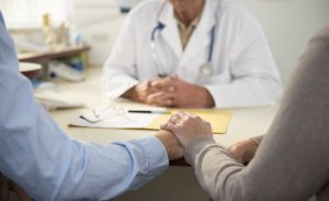 couple holding hands opposite doctor