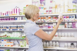 woman choosing medicine at drugstore