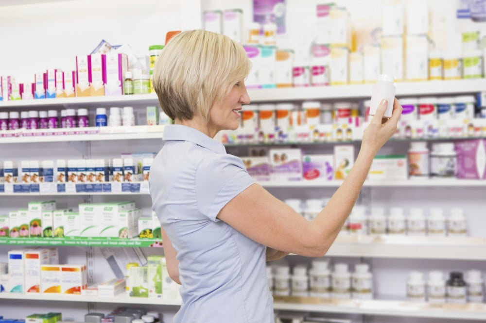 woman choosing medicine at drugstore