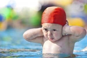 serious child with swimming pool cap hands on ears