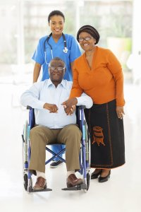 african female healthcare worker with senior couple leaving hospital