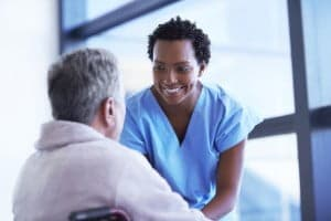 smiling nurse with patient in chair