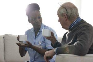 A nurse having coffee with senior man