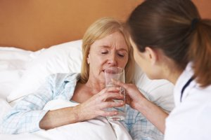 Nurse helping older woman drink