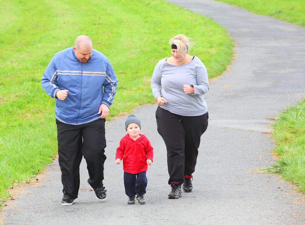 Overweight man and woman jogging with toddler