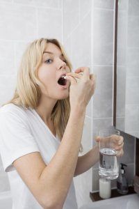 Young woman taking paracetamol in bathroom
