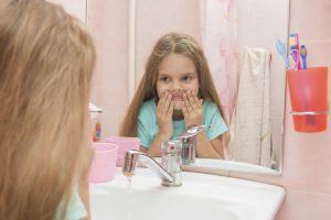 Six year old girl washes her mouth after using mouthrinse