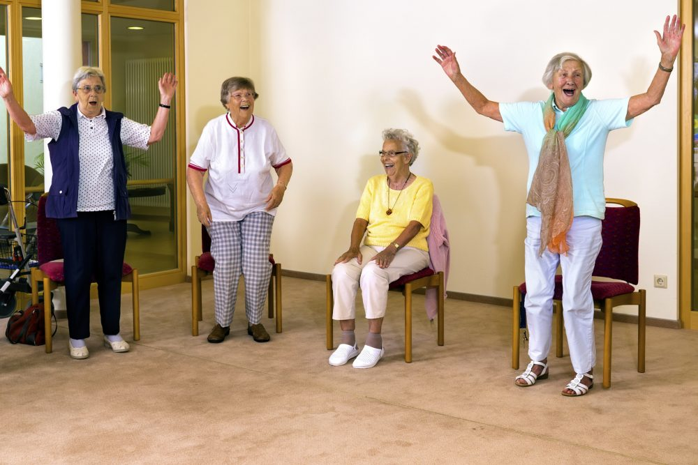 Senior women standing and sitting for exercise.