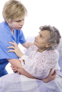 Nurse repositioning elderly woman