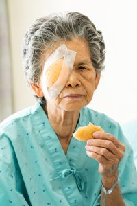 Elder female with eye patch eating bread after cataract surgery