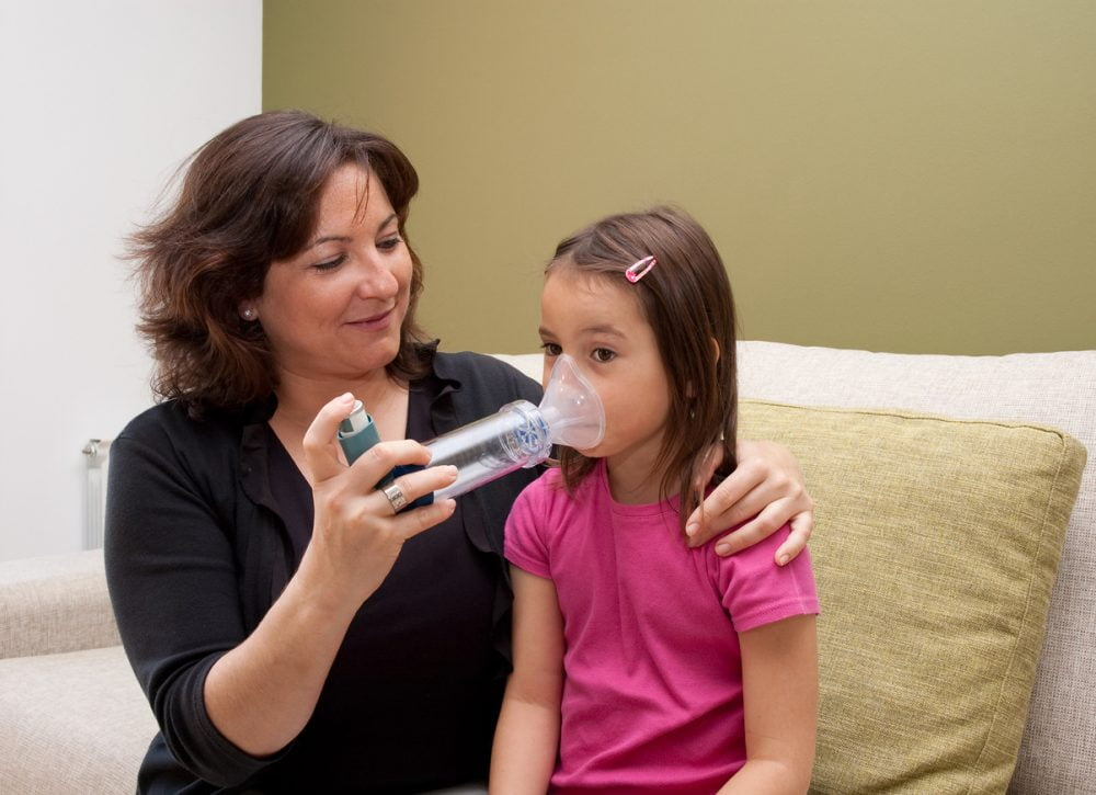 teacher using inhaler with child