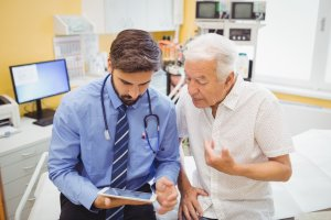 male doctor and older male patient discuss