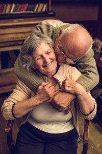 Loving senior man kissing and embracing his wife
