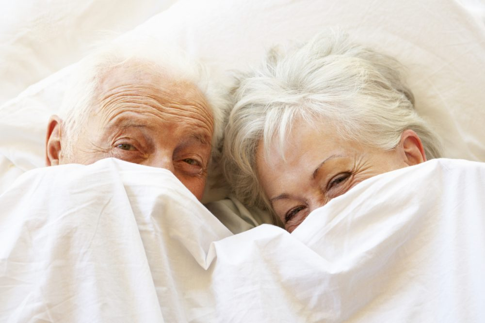 Senior Couple Relaxing In Bed Hiding Under Sheets
