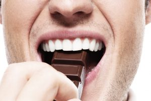 mouth of man eating chocolate