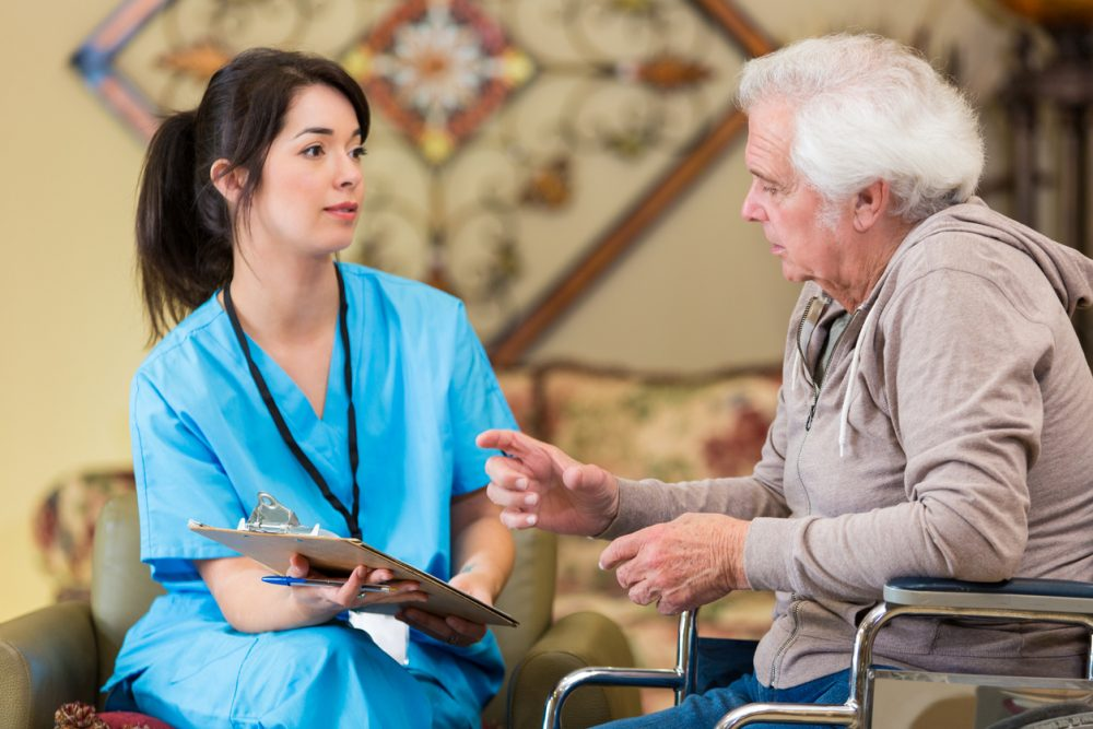 Nurse helping senior man in a wheelchair