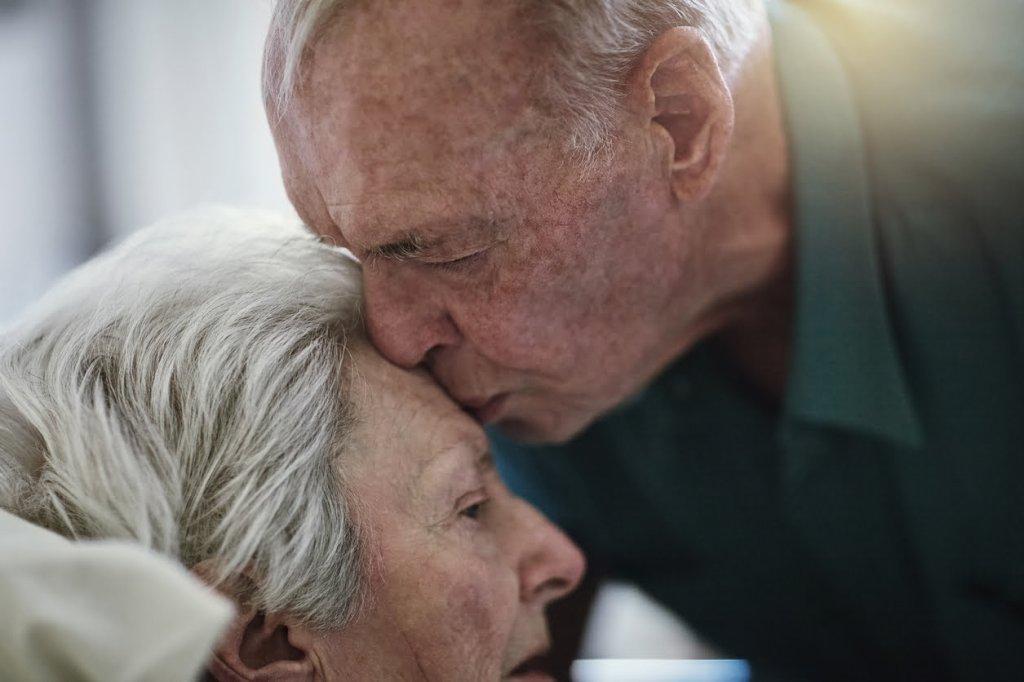 Elderly man kisses wife