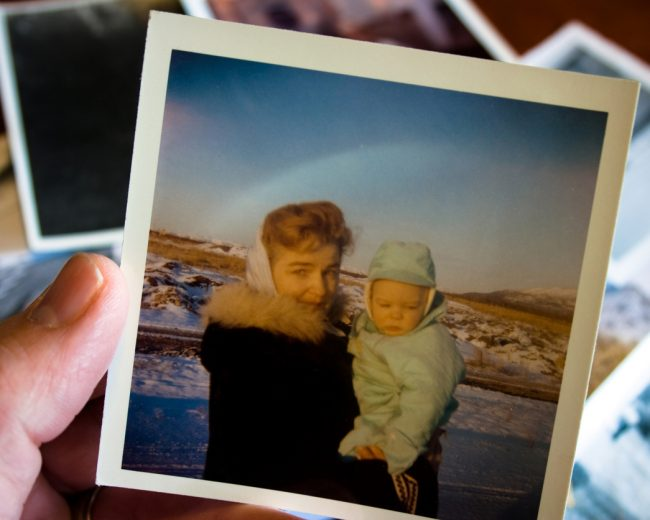 Person holding vintage photo of mother and child