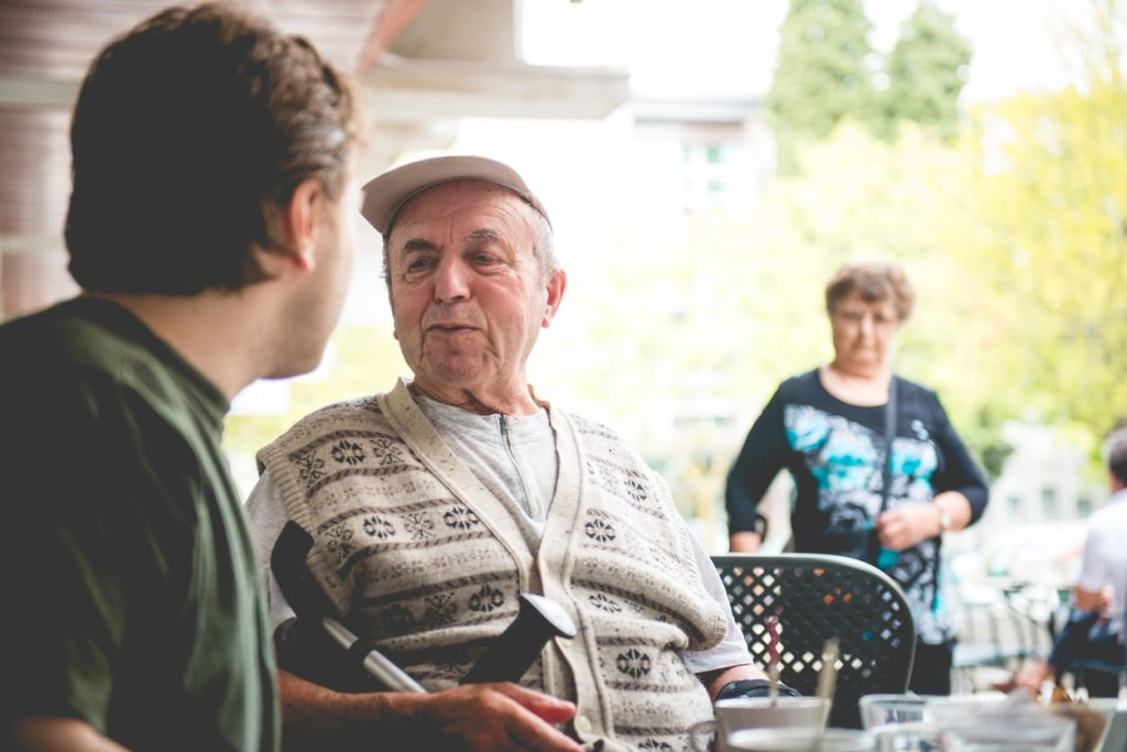 Happy Senior Man in Wheelchair and Grandson Having Coffee, Europe