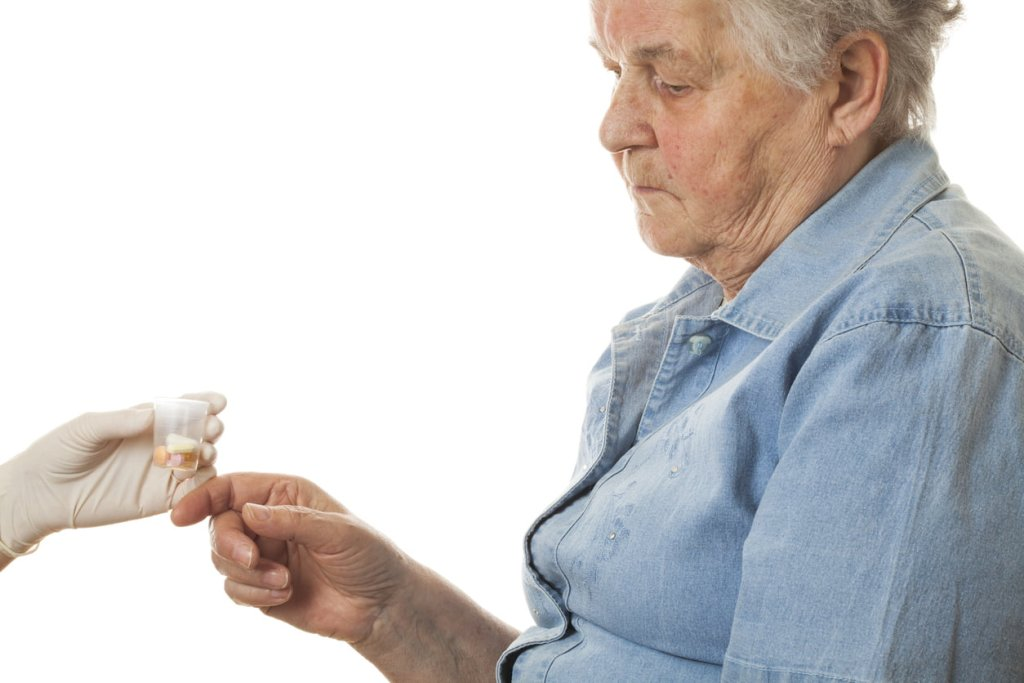 Senior woman being given pills
