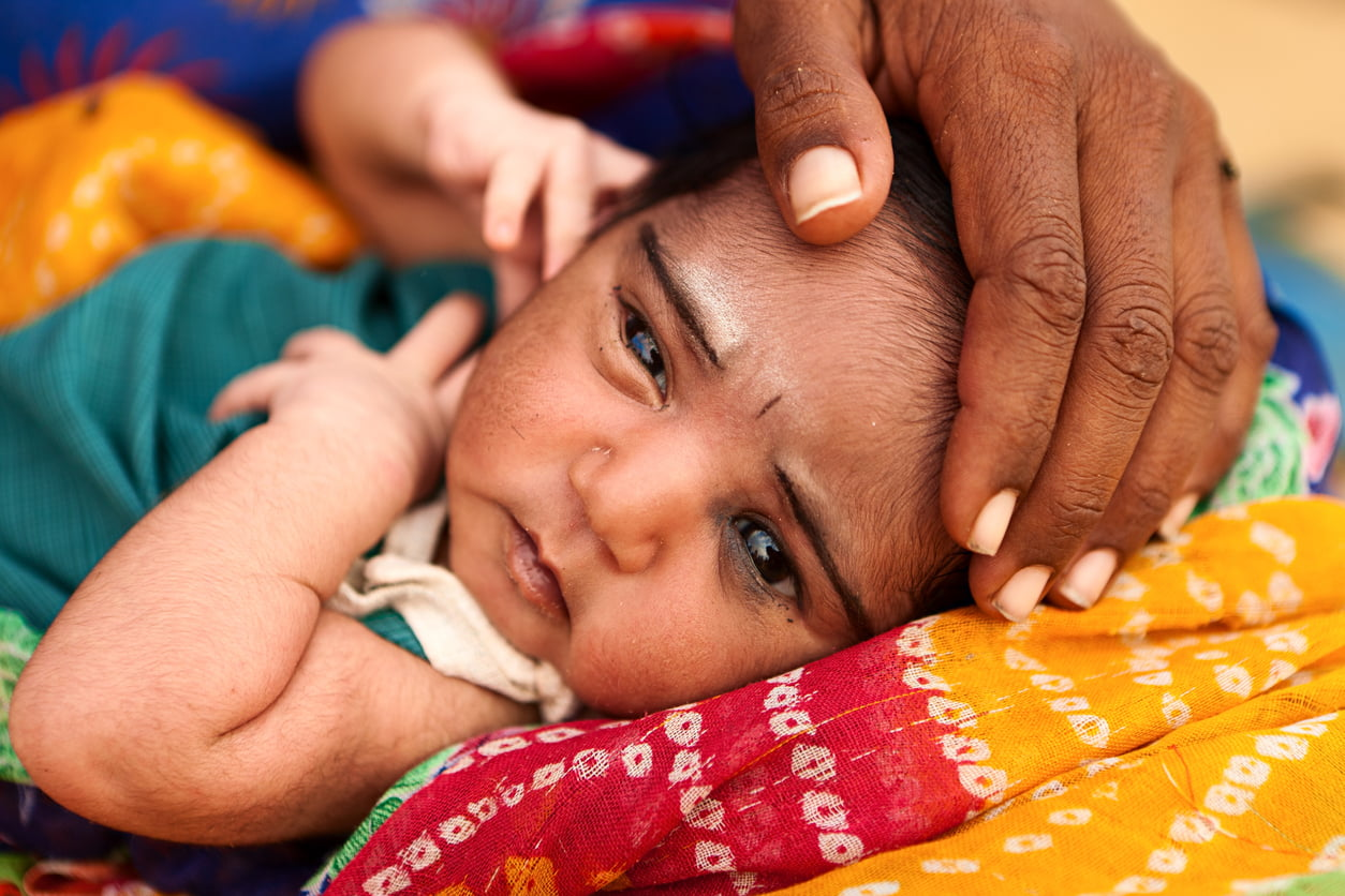 Indian woman holding her child in desert village, Rajasthan