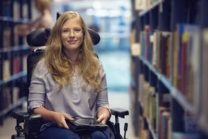 Portrait of young woman in wheelchair in library