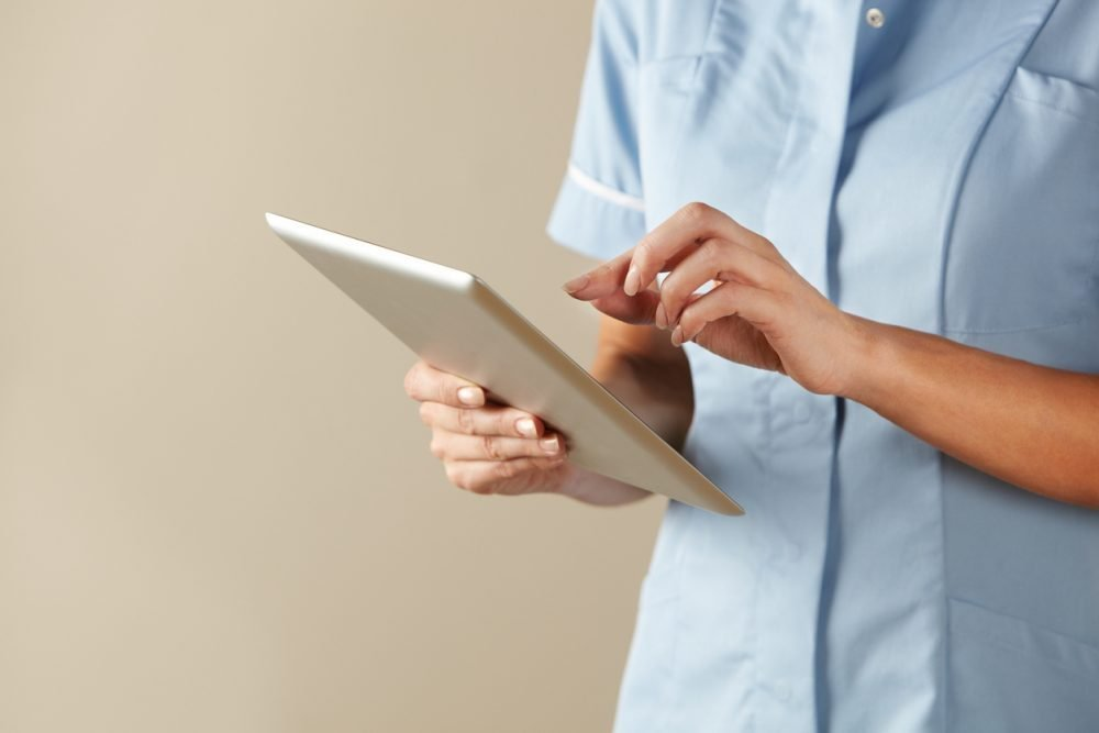 Nurse in pale blue shirt using computer tablet