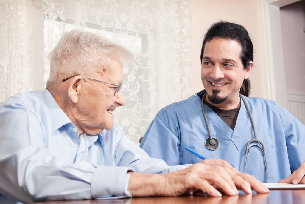 Senior man with COPD with male nurse at home