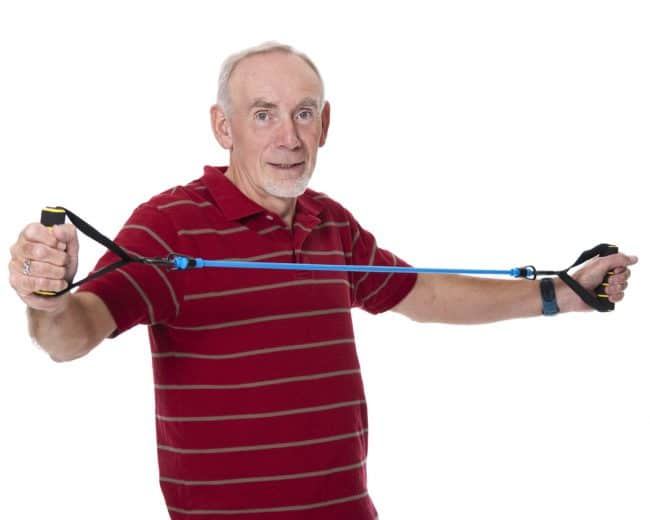 Old man exercising with resistance band