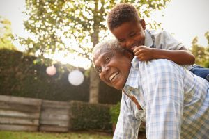 Young black boy climbing on his grandfatherâ??s back in garden
