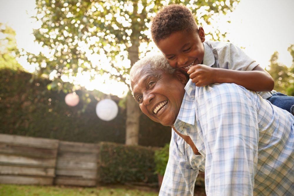 Young black boy climbing on his grandfatherâ??s back in garden