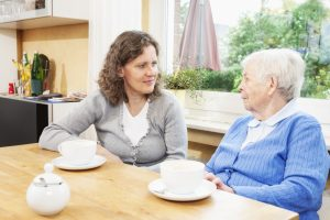 caregiver listening to senior woman