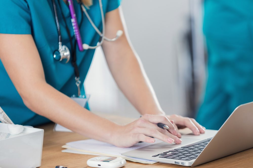 Confident nurse uses laptop in doctor's office