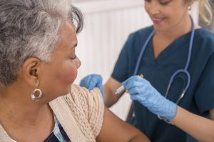 Nurse gives influenza vaccine to senior adult patient at clinic.