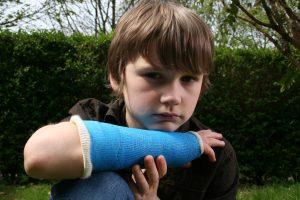 Sad boy with broken arm in blue cast