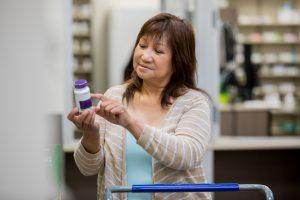 Senior female customer reading side effects of medicine in pharmacy