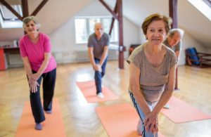 Smiling seniors doing stretching exercises in a health club.