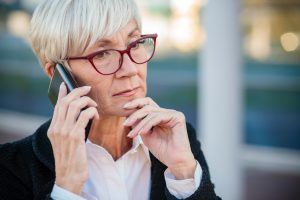 Worried mature businesswoman talking on the mobile phone, resting her arm on chin
