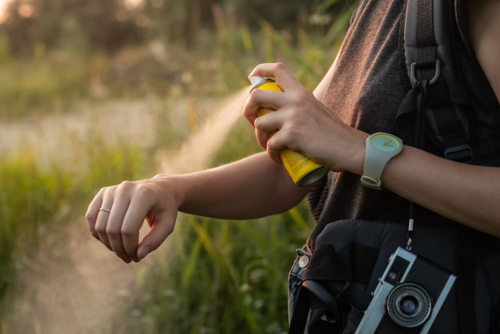 Woman using anti mosquito spray outdoors at hiking trip