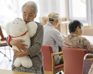 An elderly woman cuddling PARO a robotic seal