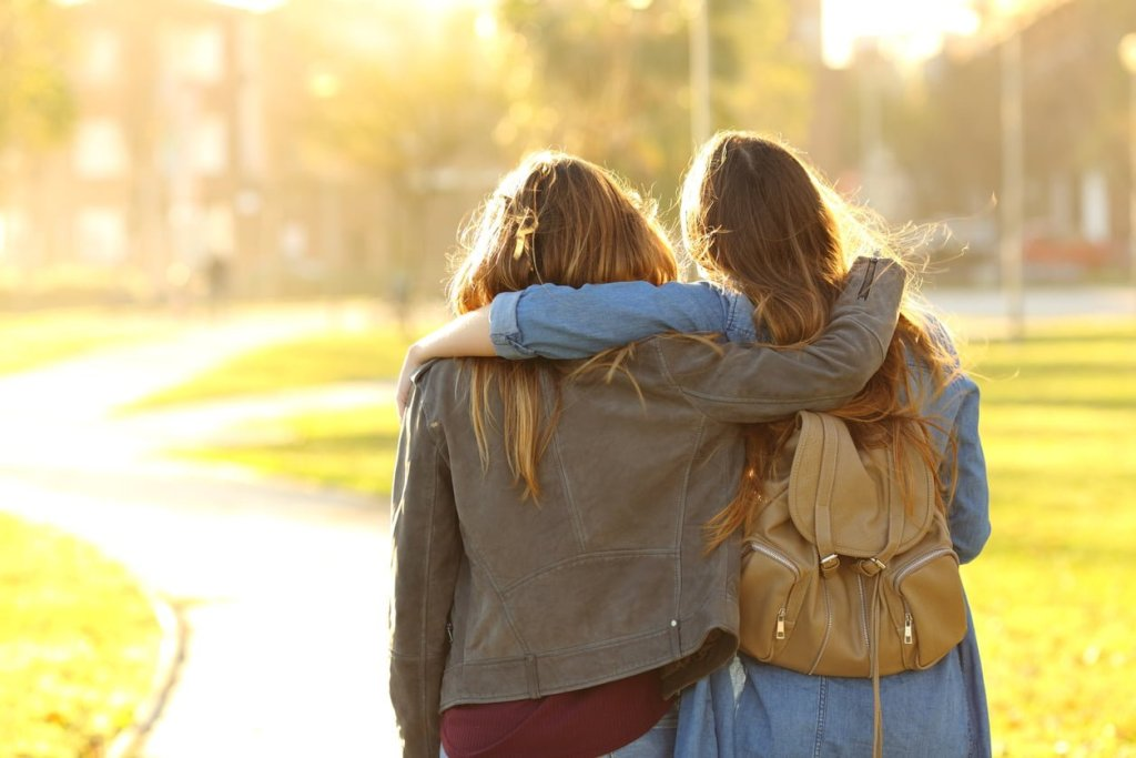 Two young woman, photographed from behind, have their arms around each other's shoulders