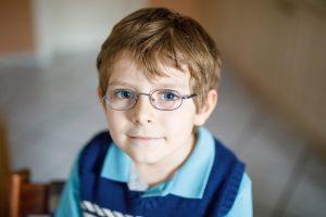 Portrait of little cute school kid boy with glasses