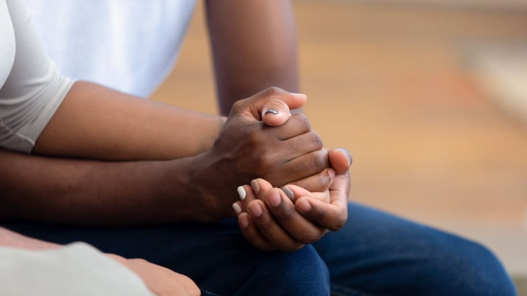 Close-up of two people's clasped hands
