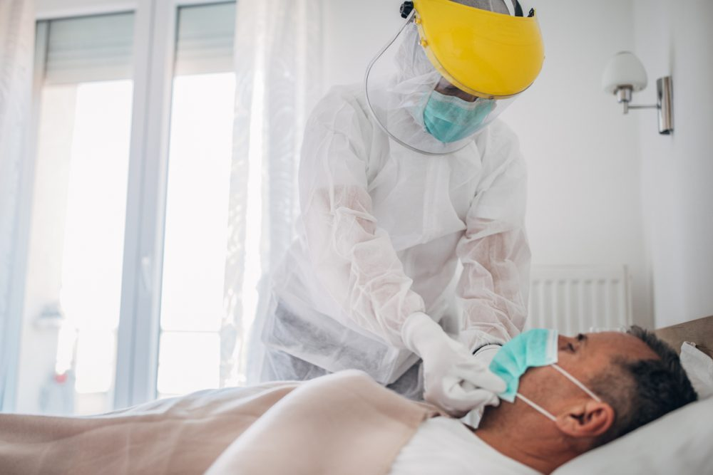 Doctor applying face mask to a senior man who is lying in hospital bed because of coronavirus infection